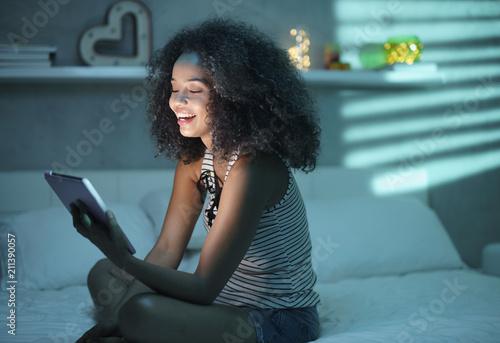 Leinwanddruck Bild Hispanic Girl Watching Film With Tablet And Laughing