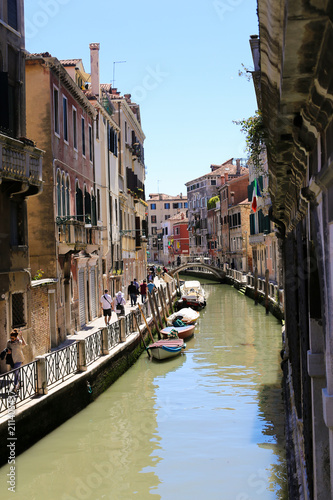 Fototapeta Venetsian street, water and cityscape, Italy. Concept of last minute tours to Venice, amazing sumer vacations and trip to Europe landmarks.