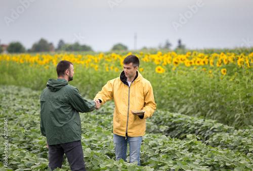 Leinwanddruck Bild Farmers shaking hands in field