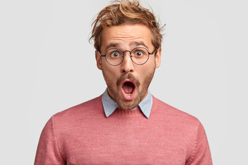 Stressed hipster male has shocked expression, realizes that his car is stolen, keeps mouth widely opened, stares through round spectacles, isolated over white background. People and emotions concept