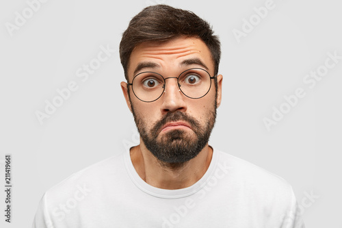 Leinwanddruck Bild Doubtful bearded male purses lips with hesitation, stares at camera with scared expression, feels cluless while recieves unexpected offer from friend, isolated over white background. Facial expression