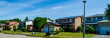 Panorama of a row of residential houses along a street, one with solar panels on the roof - 211438851