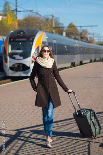 Young woman in coat with suitcase on the train station