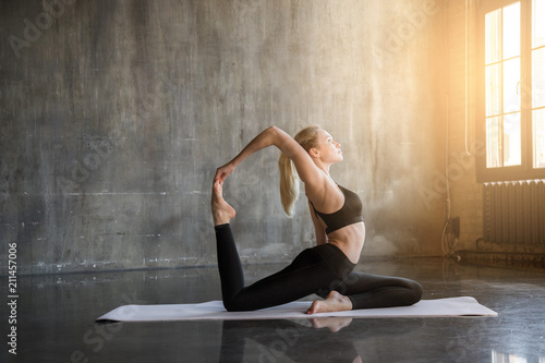 Leinwanddruck Bild Young woman doing ashtanga yoga practice in a loft studio, surrounded by bright sunlight. Beutiful girl meditating makes herself a healthy body and strengthening the spirit.