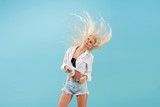 Young slender blond girl with long hair listens to music on headphones and dances, throws back her head. Carefree model in summer clothes having fun on a blue isolated background