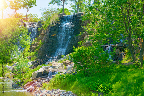 Fotobehang Groene beautiful waterfall under sunlight, many beautiful water jets surrounded by green forests.