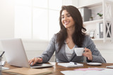 Smiling businesswoman working on laptop and drinking coffee at office - 211466443