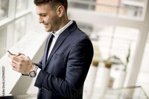 Wall mural Handsome businessman using smartphone in the office