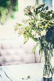 Summer flowers bunch in glass vase on table in living room with falling petals. Cozy home and house decoration - 211479207