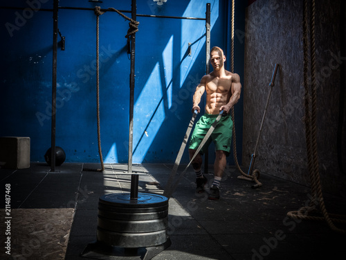 Handsome shirtless muscular young man athlete exercising with a sleigh equipment in gym