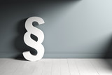 Paragrafen-Symbol an graue Wand gelehnt