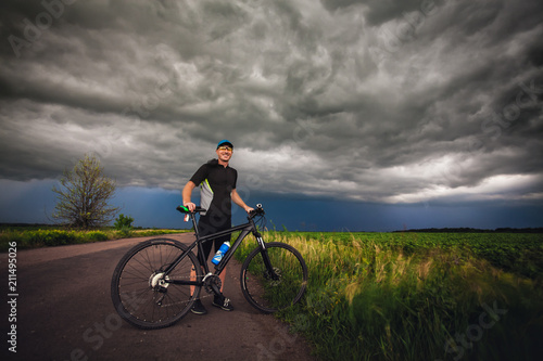 Happy man cyclist rides field road on a mountain bike. before the storm