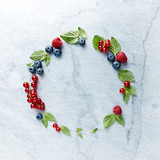 An Arrangement of fresh raspberries, blueberries, red currant and mint leaves on gray marble background. Flat lay.  - 211497485