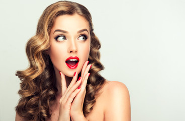 Shocked and surprised girl looking to the side presenting  your product . Curly hair woman amazed .Beautiful girl  with curly hair and red nails manicure. Expressive facial expressions