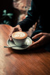 Latte art coffee and woman's hands - 211498884