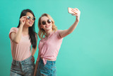 diversity, race, ethnicity, relationship concept - happy female couple, blonde caucasian and brunette Thai taking selfie with smartphone over blue background with copyspace - 211499443