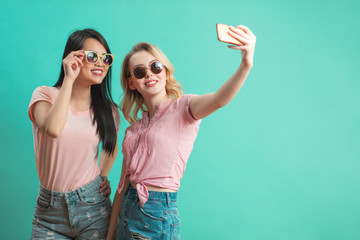 diversity, race, ethnicity, relationship concept - happy female couple, blonde caucasian and brunette Thai taking selfie with smartphone over blue background with copyspace © alfa27