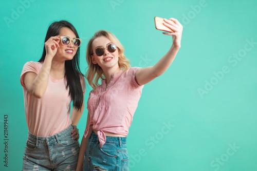 różnorodność, rasa, pochodzenie etniczne, związek pojęcie - szczęśliwa żeńska para, blondynka caucasian i brunetka Tajlandzki bierze selfie z smartphone nad błękitnym tłem z copyspace