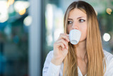 Beautiful woman having a coffee in a cafe - 211508837