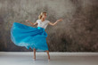 Beautiful young woman in a lush blue skirt, whirling and dancing.