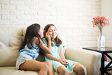 Happy little girls whispering and sharing a secret - 211523242