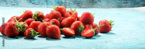 Heap of fresh strawberries on blue background - 211526631