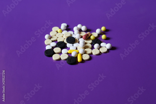 Assorted pharmaceutical medicine pills, tablets and capsules on purple background - 211527216