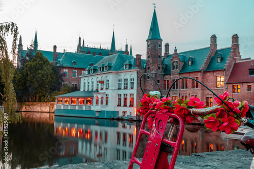 bike decorated with flowers on the background of the canal and the main view of the brugge - 211529689