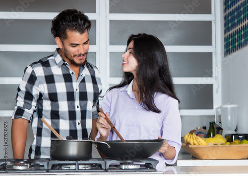 Wall mural Young love couple cooking at kitchen