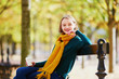Leinwanddruck Bild - Happy young girl in yellow scarf walking in autumn park