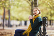 Leinwanddruck Bild - Happy young girl in yellow scarf walking in autumn park