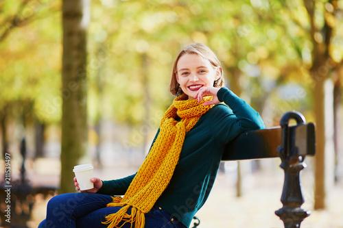 Leinwanddruck Bild Happy young girl in yellow scarf walking in autumn park