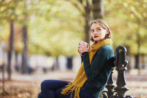 Leinwanddruck Bild Happy young girl in yellow scarf walking in autumn park