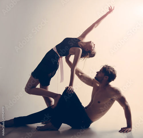 Enjoy dancing together. Muscular man and cute woman perform modern dance. Young woman and man dance love and romance. Couple of dancers. Dance school training. Romantic relationship - 211542878