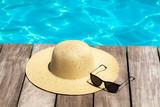 chapeau et lunettes au bord d'une piscine - 211543657