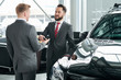 Salesman passing key to businessman in auto at dealership