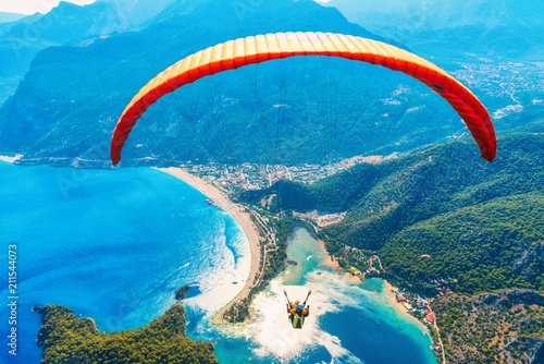 Paragliding in the sky. Paraglider tandem flying over the sea with blue water and mountains in bright sunny day. Aerial view of paraglider and Blue Lagoon in Oludeniz, Turkey. Extreme sport. Landscape © den-belitsky