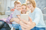 Warm toned portrait of loving young family with cute little son playfully taking selfie at home  in sunlight - 211544669