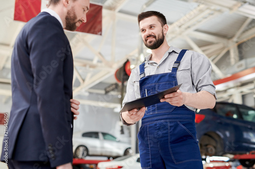 Low angle portrait of smiling bearded mechanic talking to businessman standing in clean car service and repair center