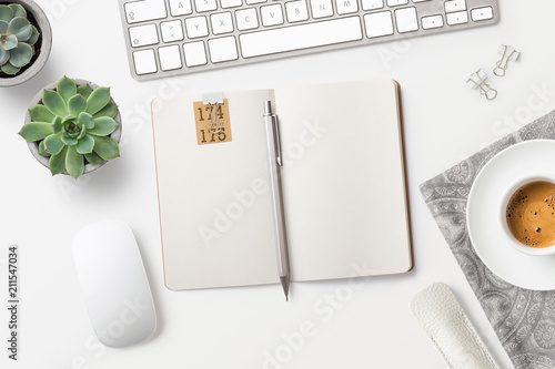 Leinwanddruck Bild modern minimalist workspace / desktop with blank open notebook, coffee, office supplies and succulents, top view