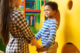 Colorful portrait of cute African American boy holding hands with girl while having fun playing in children center - 211576497