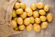 Leinwanddruck Bild - Sack of fresh raw potatoes on wooden background, top view.