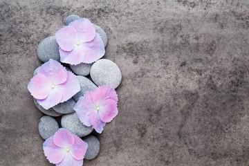 Spa flowers and massage stone, on grey background. © gitusik