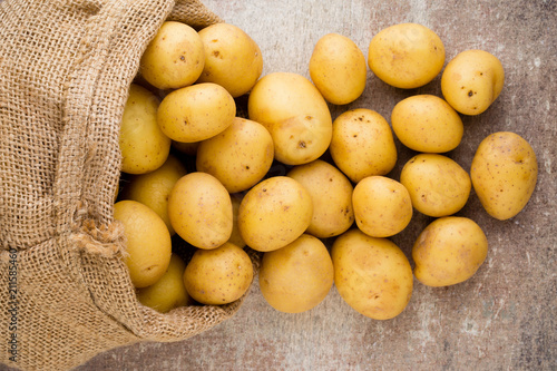 Wall mural Sack of fresh raw potatoes on wooden background, top view.