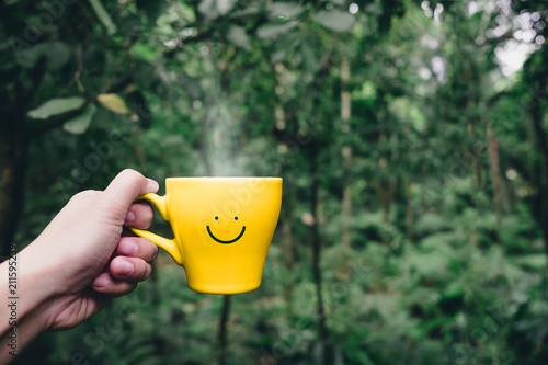 Leinwanddruck Bild Hand holding hot yellow coffee cup with hand drawn smile face on cup at tropical nature forest,Leisure lifestyle.