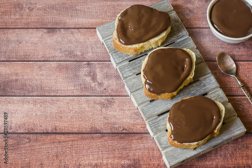 Bread baguette with chocolate cheese paste on a wooden stand. Copy space