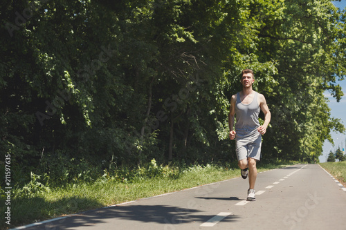 Aluminium Fitness Young man jogging on treadmill in park, copy space