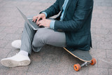 cropped view of man using laptop and sitting on skateboard