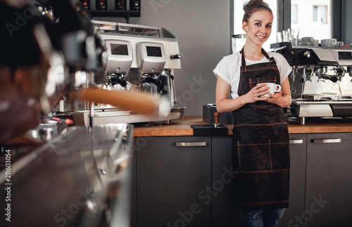 Leinwanddruck Bild Young smiling cafe business owner standing at bar in coffee shop