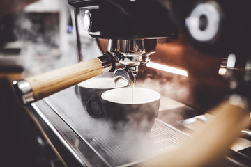 Espresso poruing from coffee machine at cafe